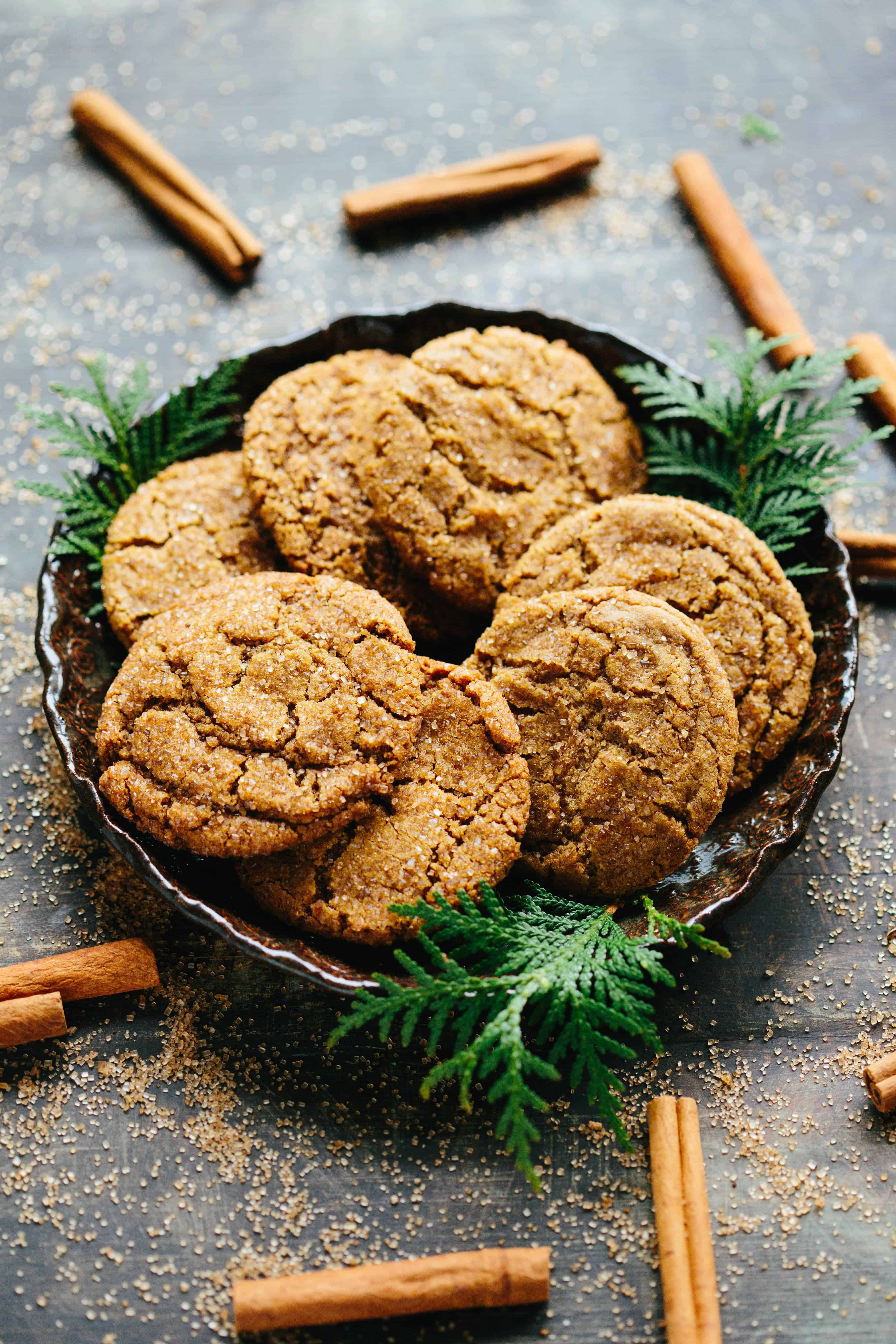 plate of Brown Butter Ginger Molasses Cookies decorated with cinnamon sticks and evergreen leaves