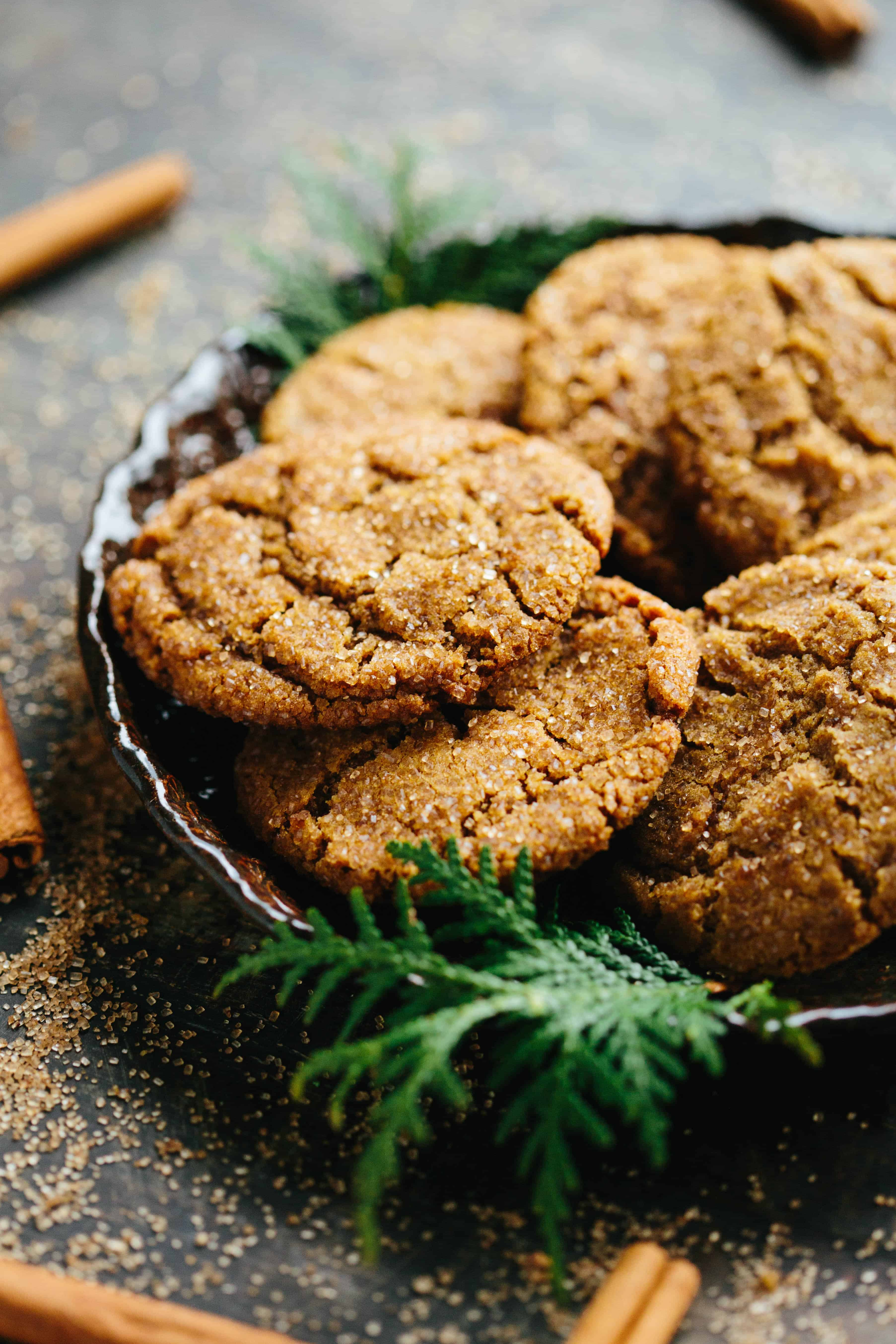 A plate of Brown Butter Ginger Molasses Cookies decorated with evergreen leaves