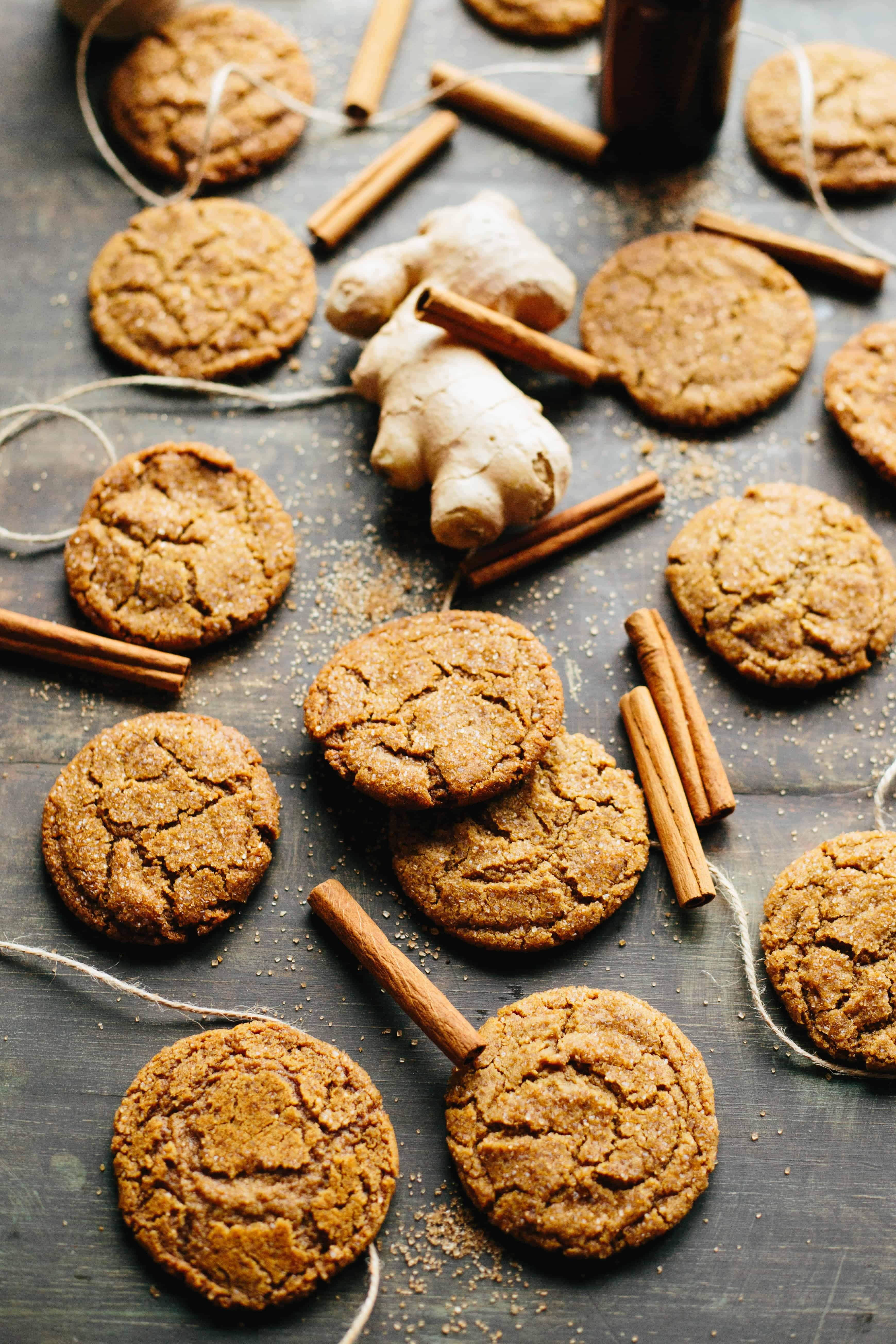 Brown Butter Ginger Molasses Cookies randomly spread out on a table with cinnamon sticks, fresh ginger and twine