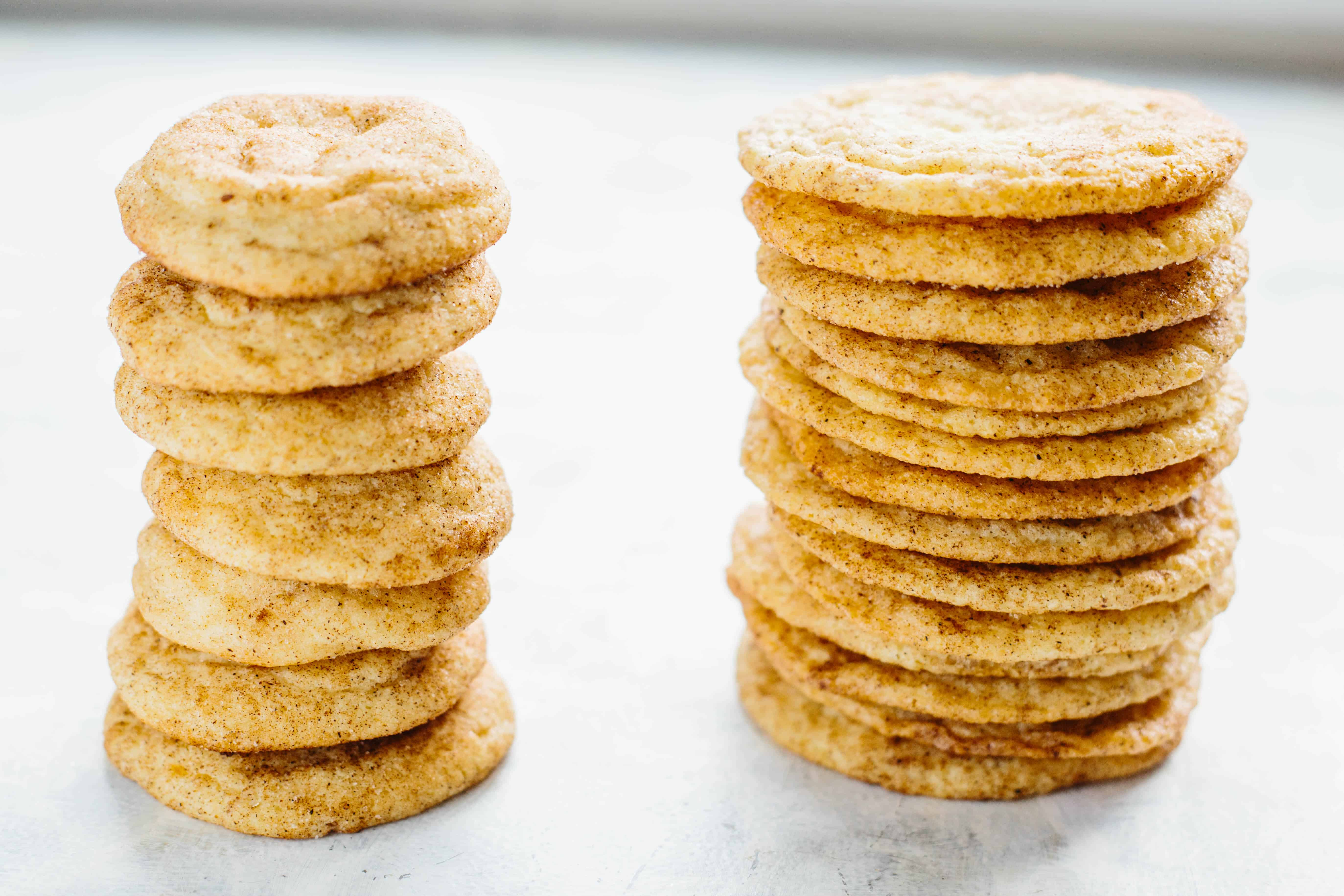 Two stacks of snickerdoodles, one is thick and chewy cookies and the other thinner and crispy.