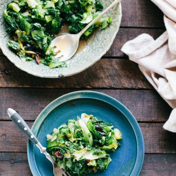 Blue dinner plate of escarole and olive salad next to a large serving bowl.