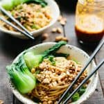 A bowl of dan dan noodles and baby bok choy with chopsticks.