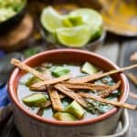 A brown bowl of chicken tortilla soup topped with diced avocado and fried tortilla strips.