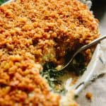 Close up of kale gratin with crunchy topping in a casserole dish.