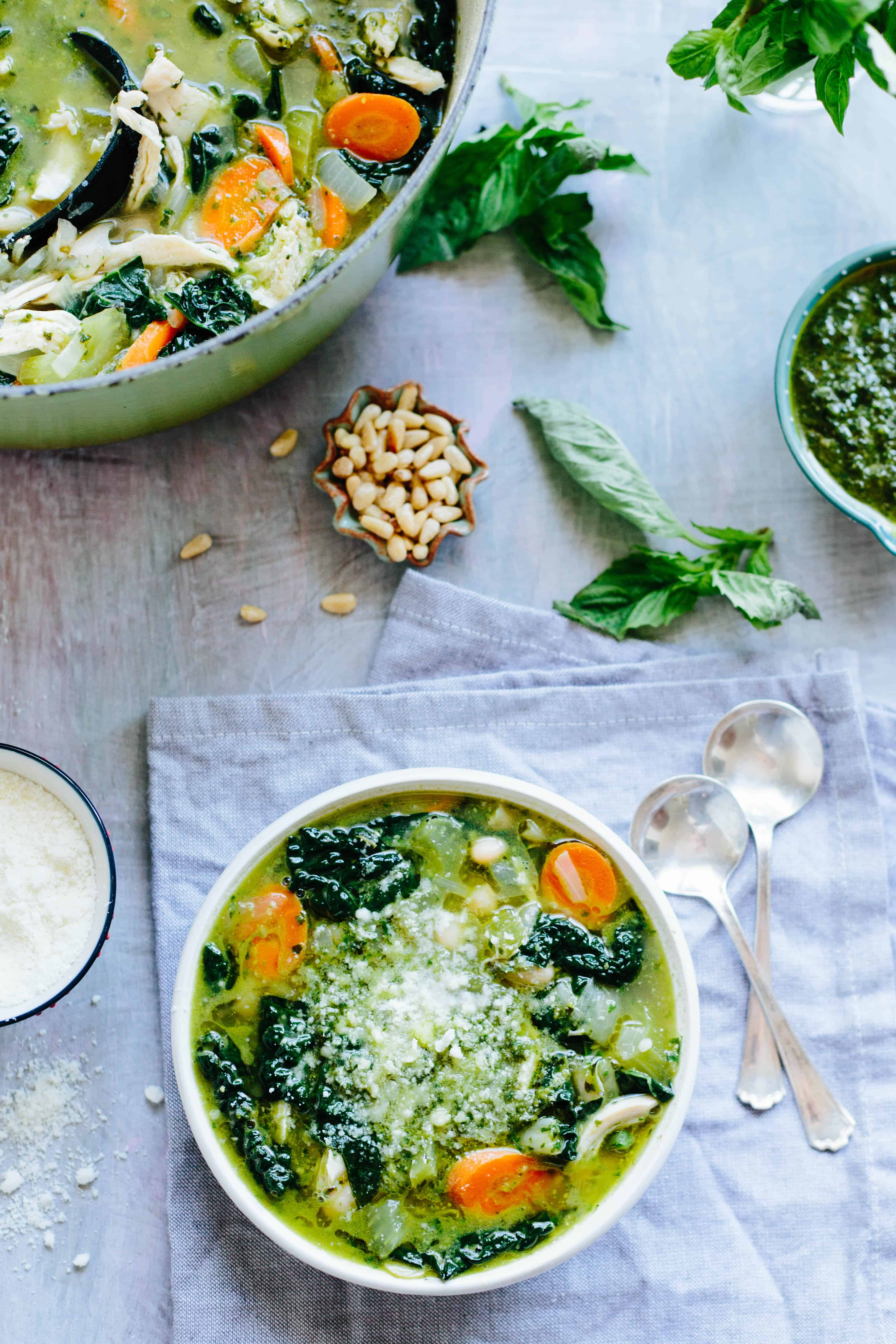 Top view and vertical shot of a bowl of pesto chicken kale soup.