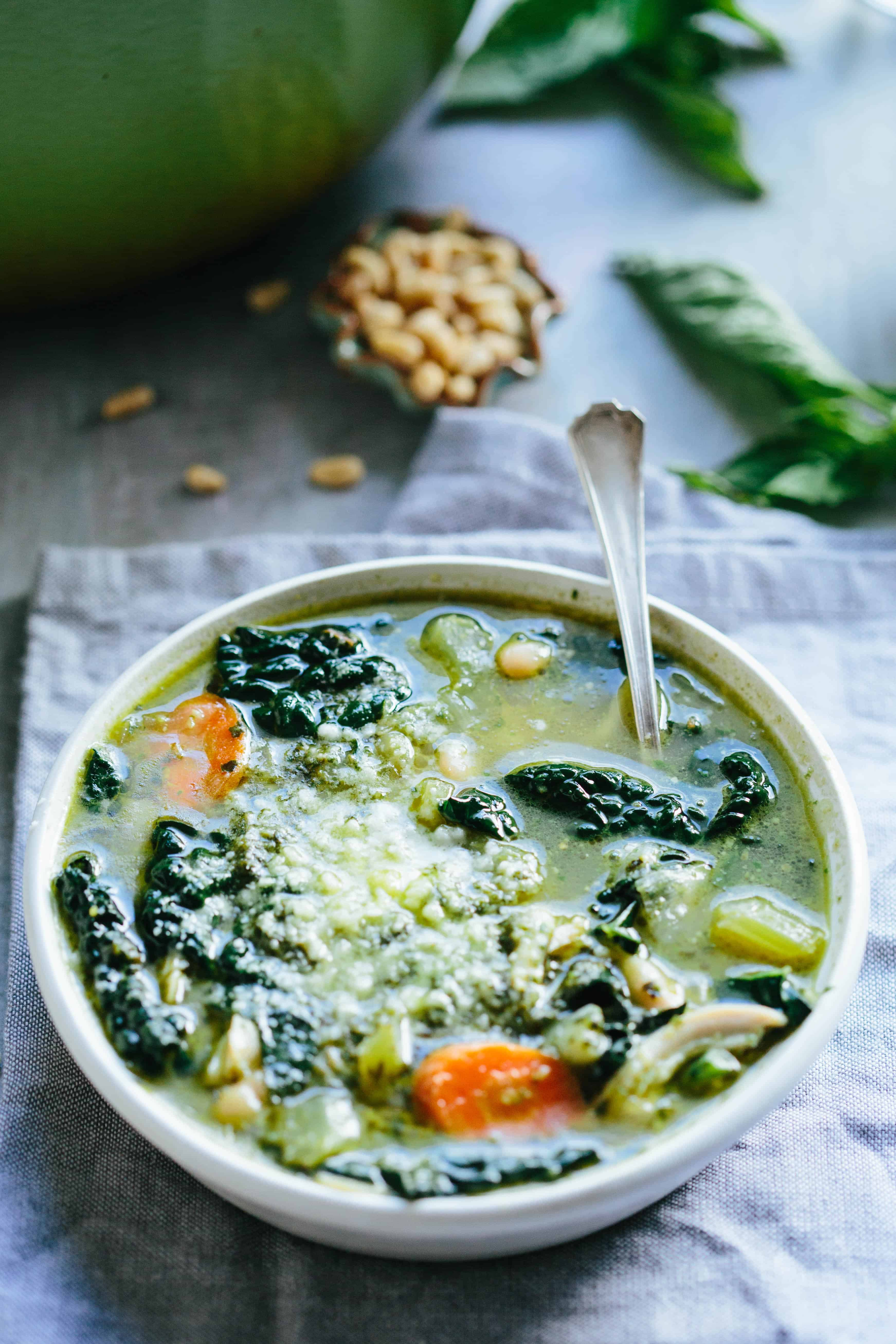 Close up of a bowl of chicken white bean soup with carrots and kale.