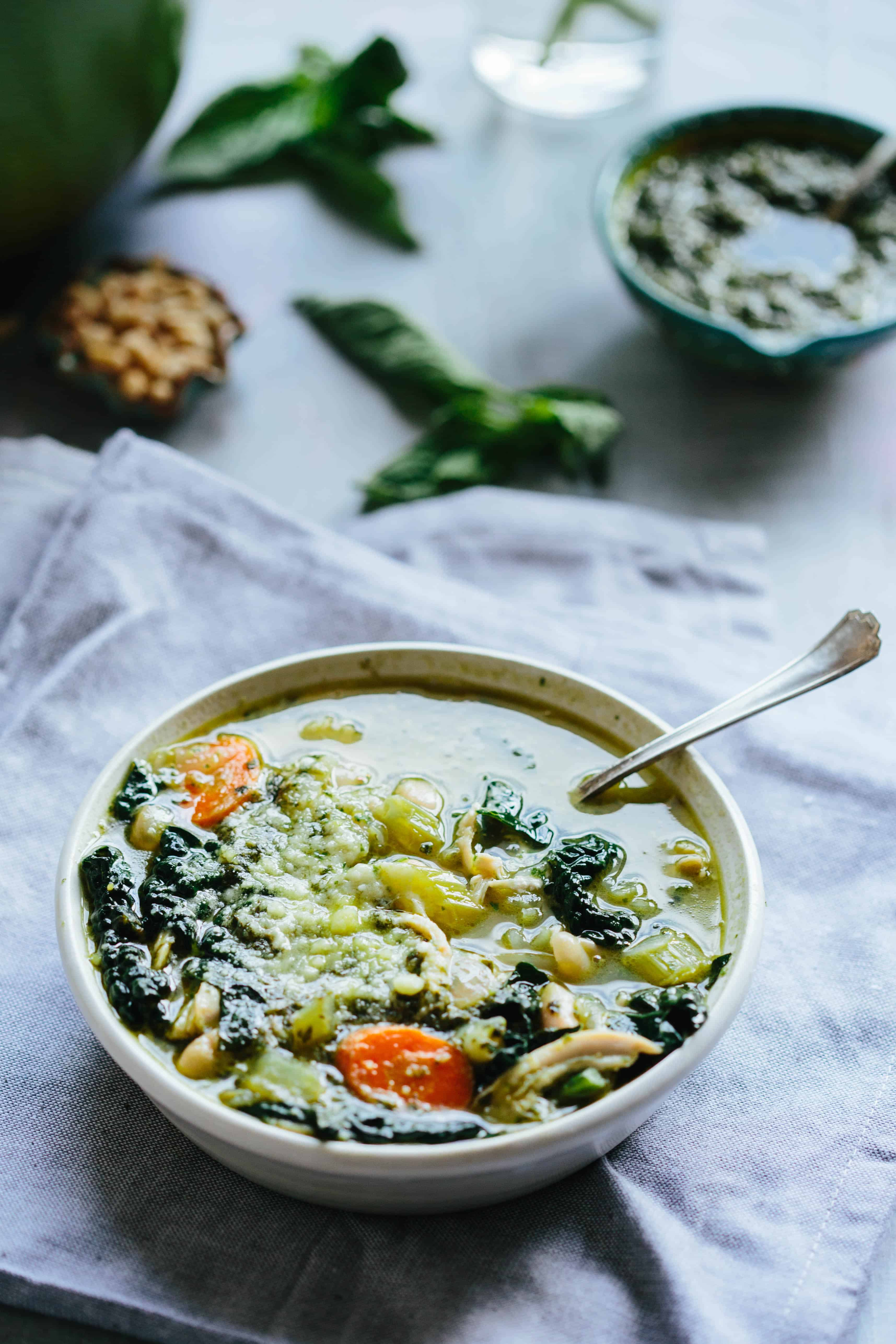 Angled shot of a bowl of chicken kale white bean soup that has carrots and celery.