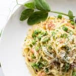 Top view of linguini carbonara with peas in a shallow white bowl.