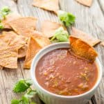 Fresh fried tortilla chips on a table next to a bowl of authentic Mexican tomato salsa.