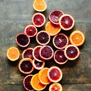 Colorful citrus cross sections spread out on a wooden tabletop.