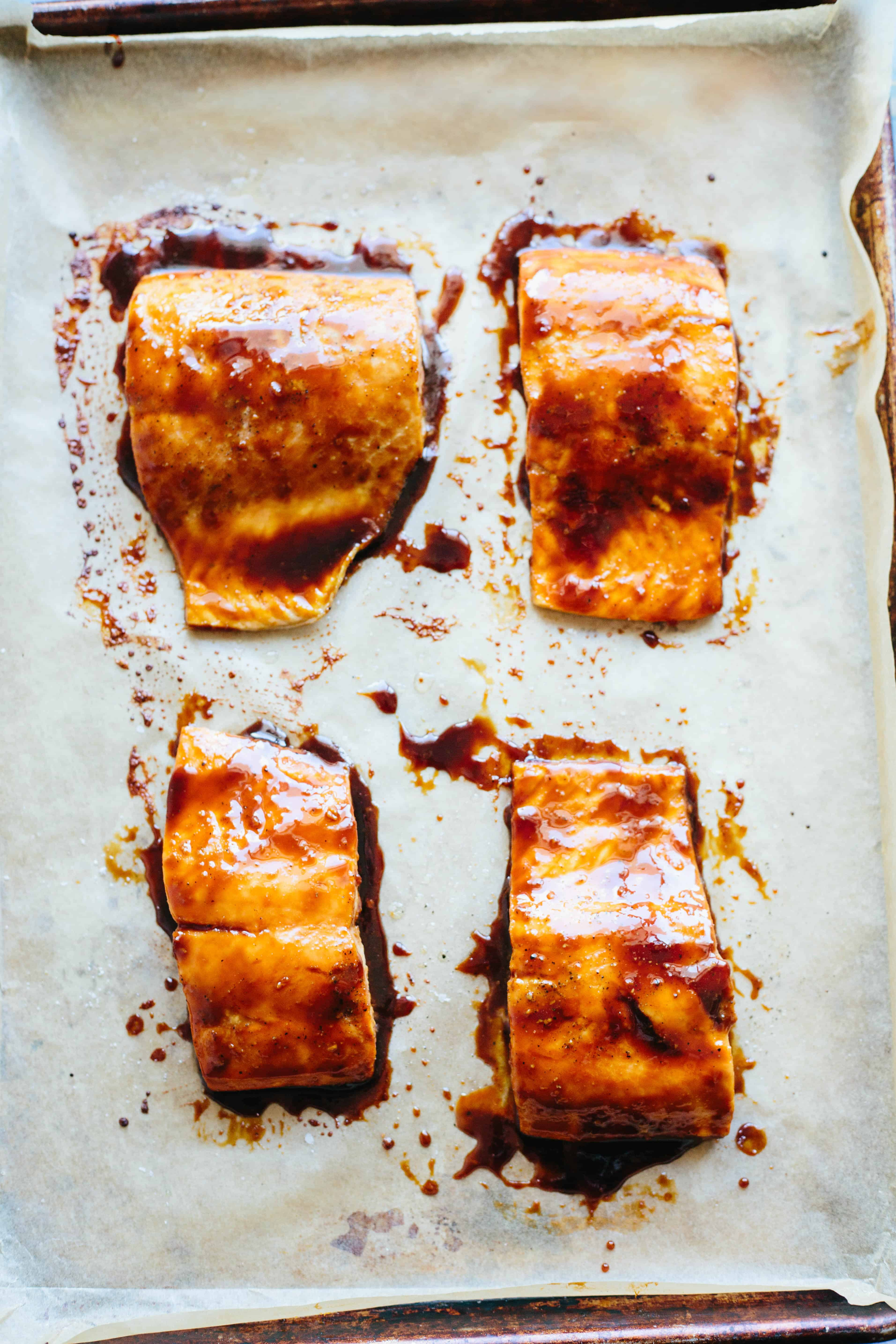 Four soy-glazed salmon filets on a parchment-lined baking sheet.