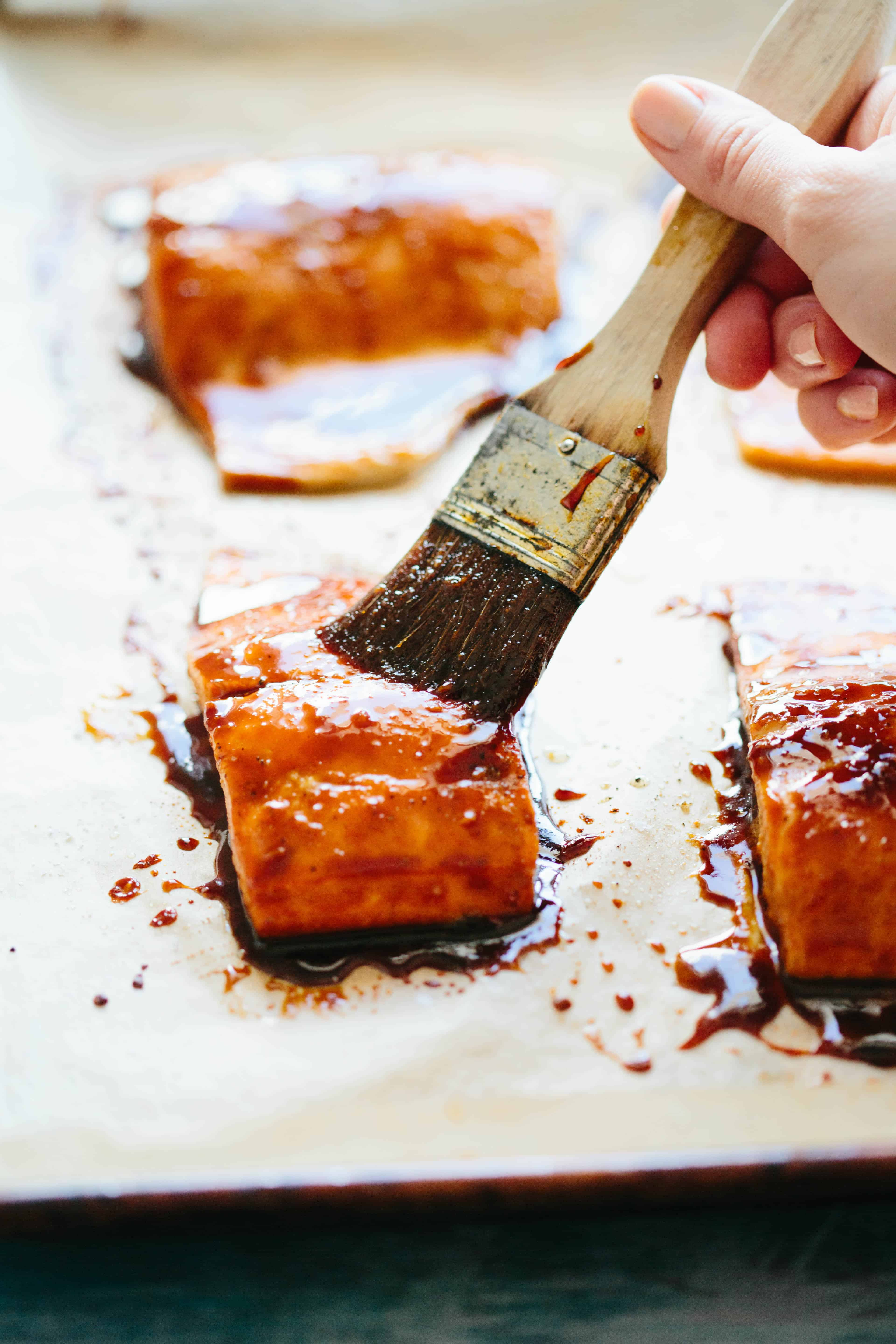 Using a pastry brush to add soy glaze to a salmon fillet.