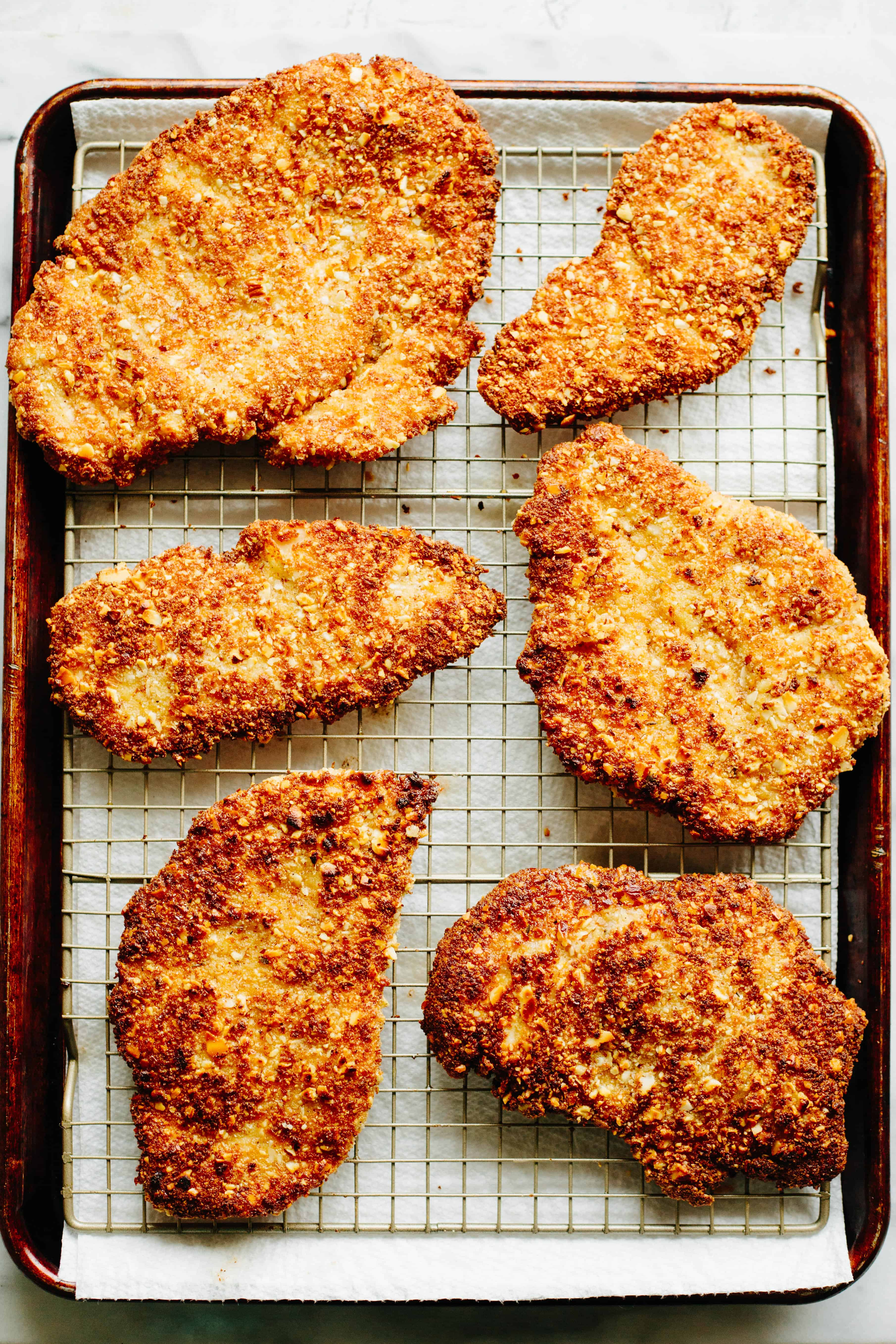 Almond breaded chicken cutlets draining on a wire rack over a baking sheet.