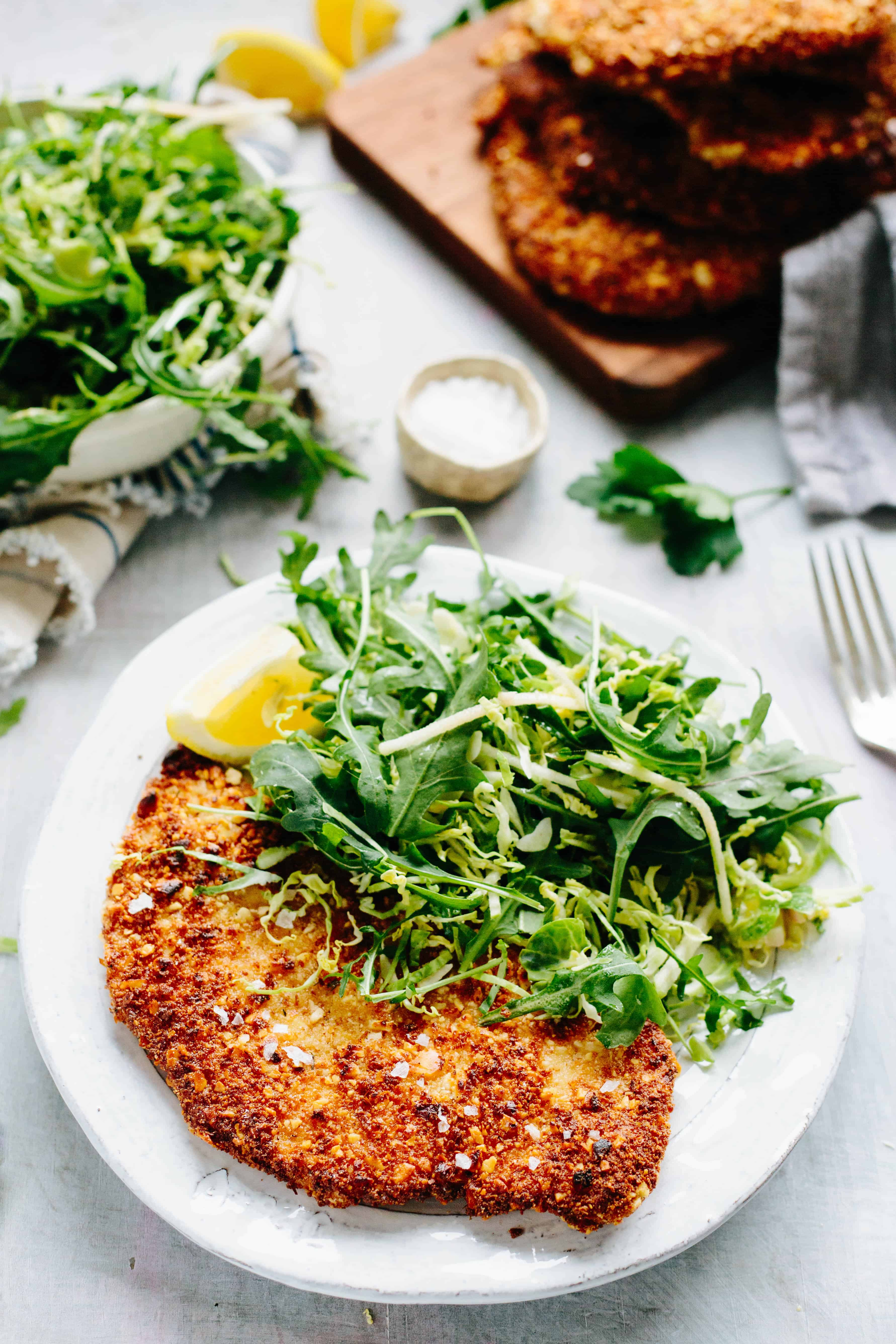 Vertical shot of a white dinner plate containing arugula salad and a breaded chicken cutlet.