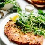 Super close up shot of a breaded chicken cutlet and arugula salad on a white dinner plate.