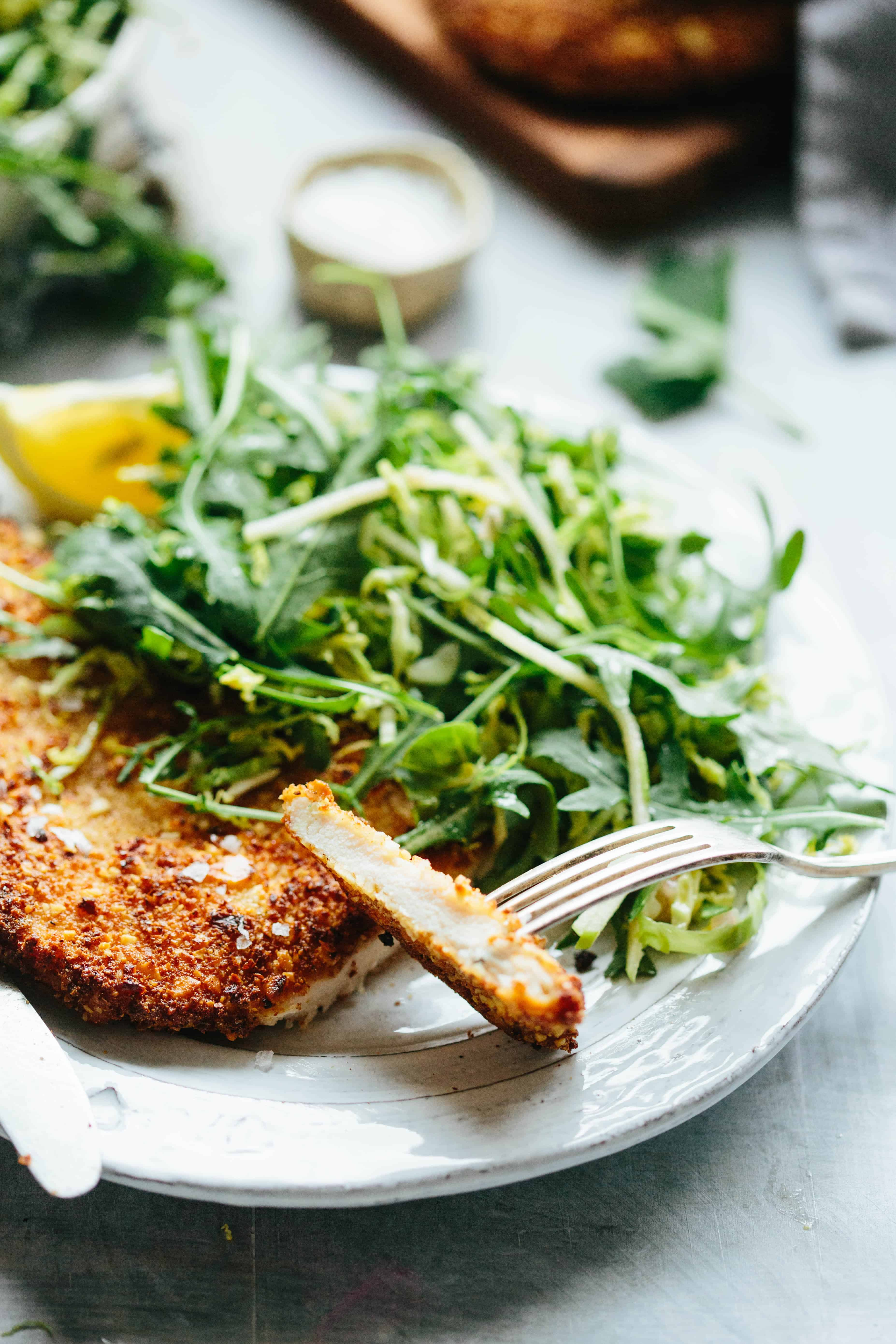 A fork holding a slice off an almond-crusted chicken cutlet next to arugula salad.