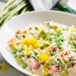 White bowl filled with spring vegetable risotto.