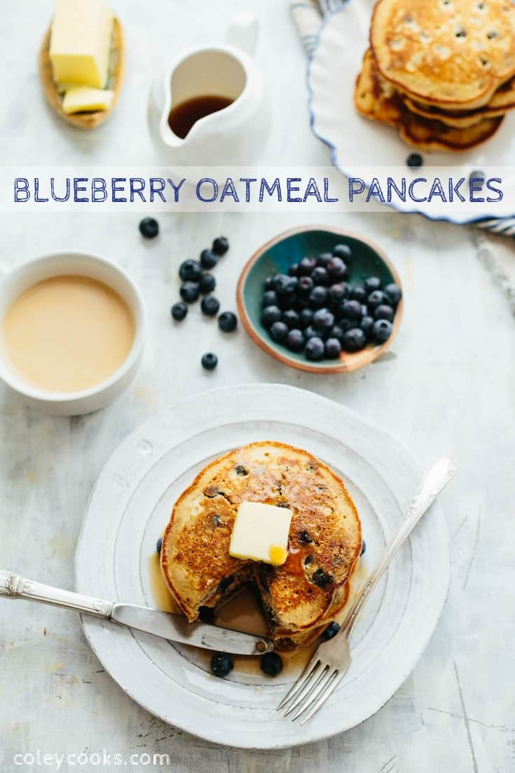 Vertical Pinterest image of blueberry oatmeal pancakes next to bowls of batter and blueberries.