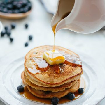 Pouring maple syrup over a stack of blueberry oatmeal pancakes on a plate.