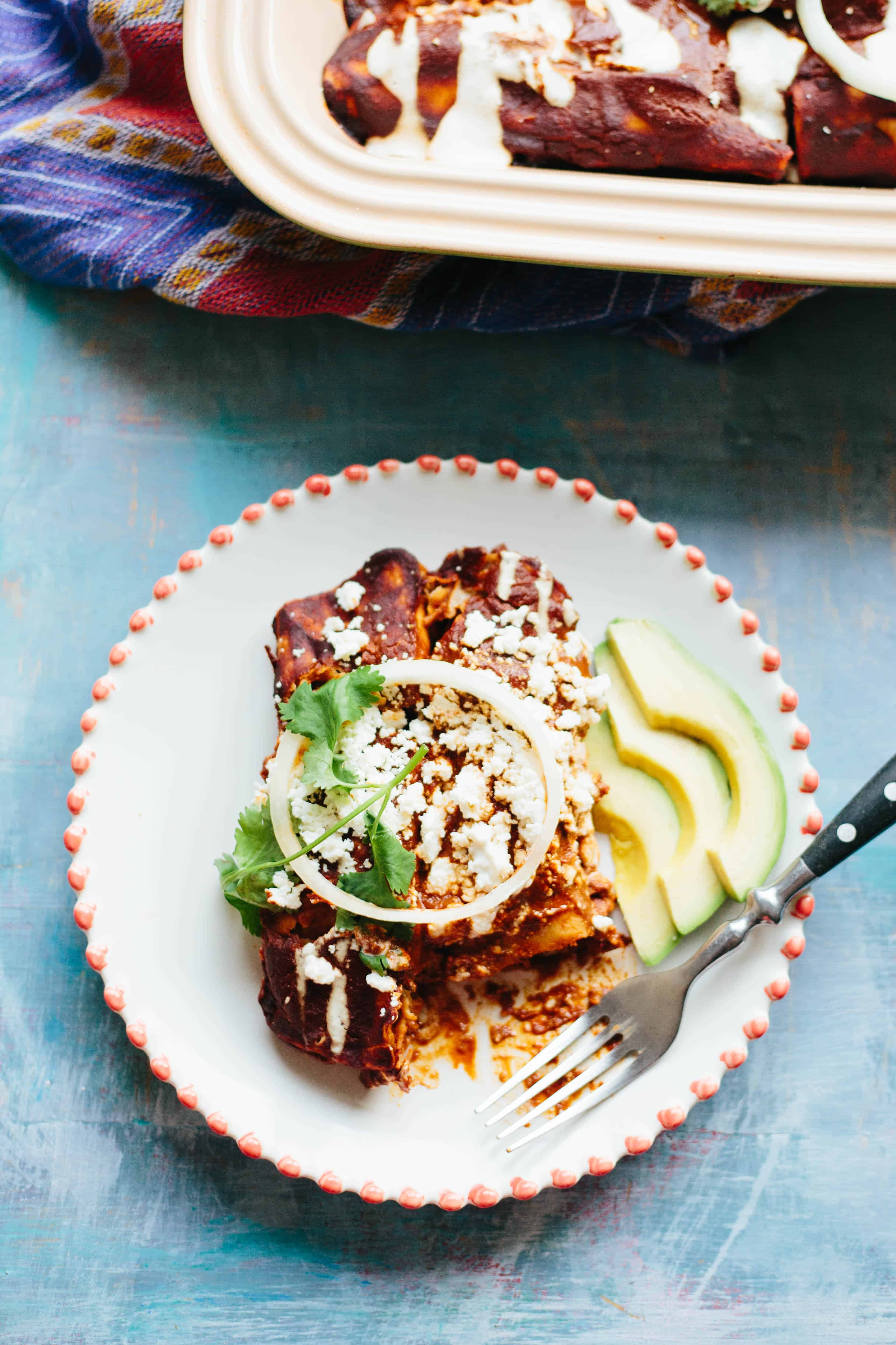 Full dinner plate of a chicken mole enchilada topped with chihuahua cheese, cilantro, and sliced avocado.