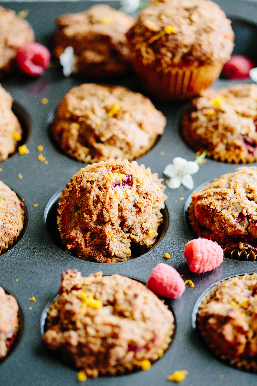 Close up of an orange raspberry Paleo muffin tipped in a muffin tin.