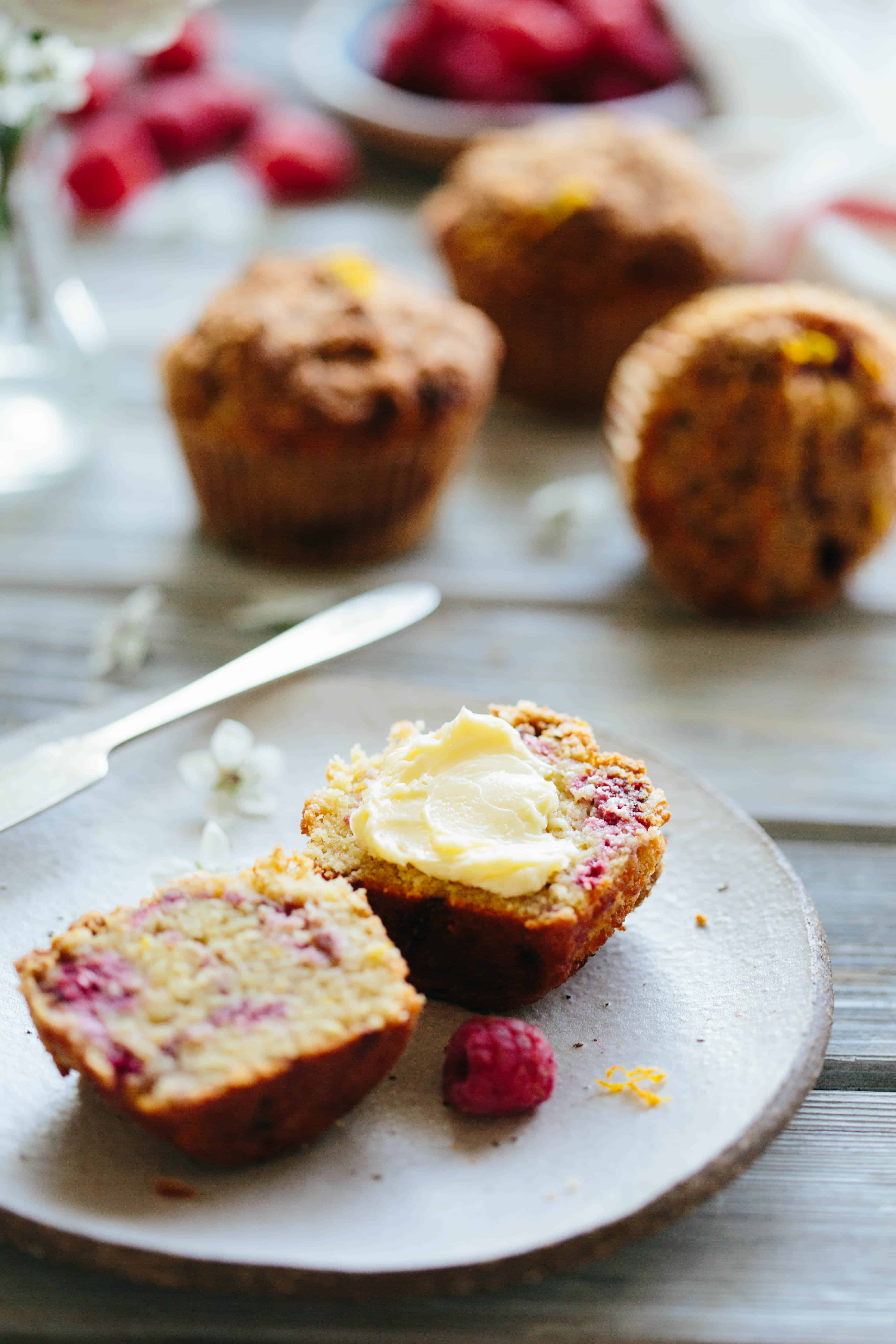 Close up of a Paleo orange raspberry muffin split in half and buttered.