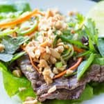 Close up of Thai beef lettuce wraps on a white plate.