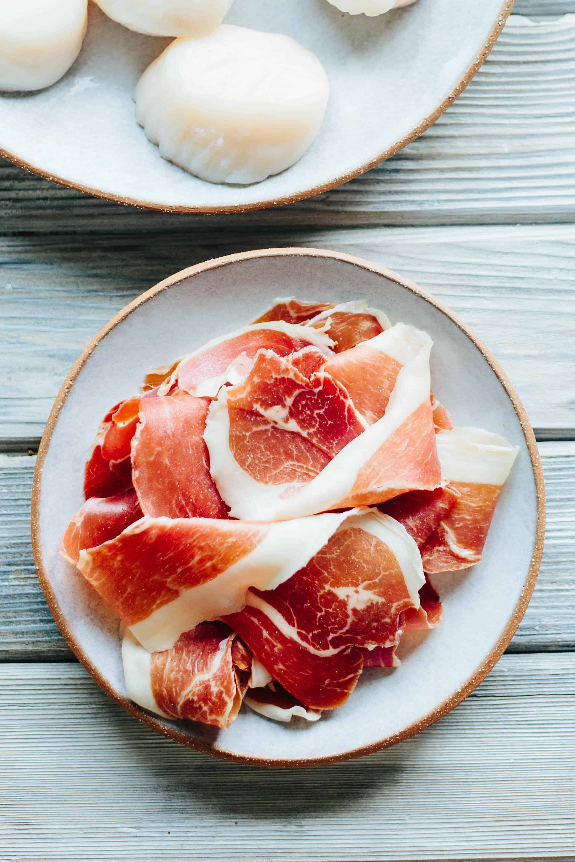 Bayonne ham slices stacked on a round plate.