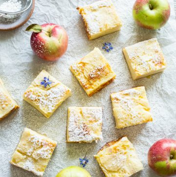 Sliced custard cream apple bars dusted with powdered sugar.