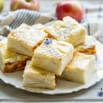 Side view of sliced apple custard bars stacked on a plate.