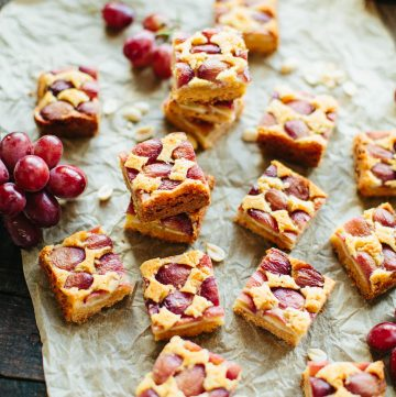 Sliced peanut butter grape bars on a sheet of parchment paper.