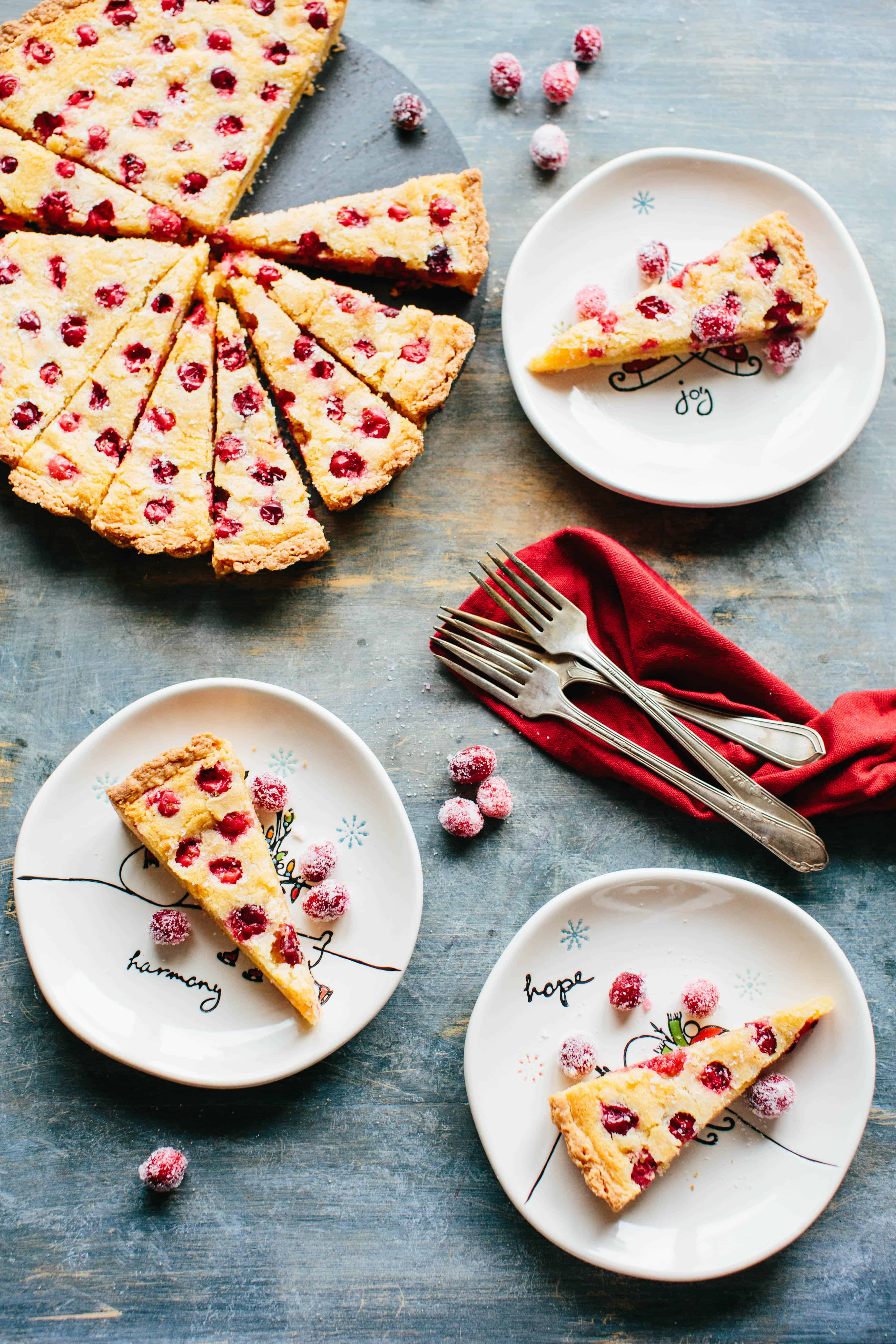 A table of food with several plates of cranberry frangipane tart with a red napkin, forks and sugared cranberries