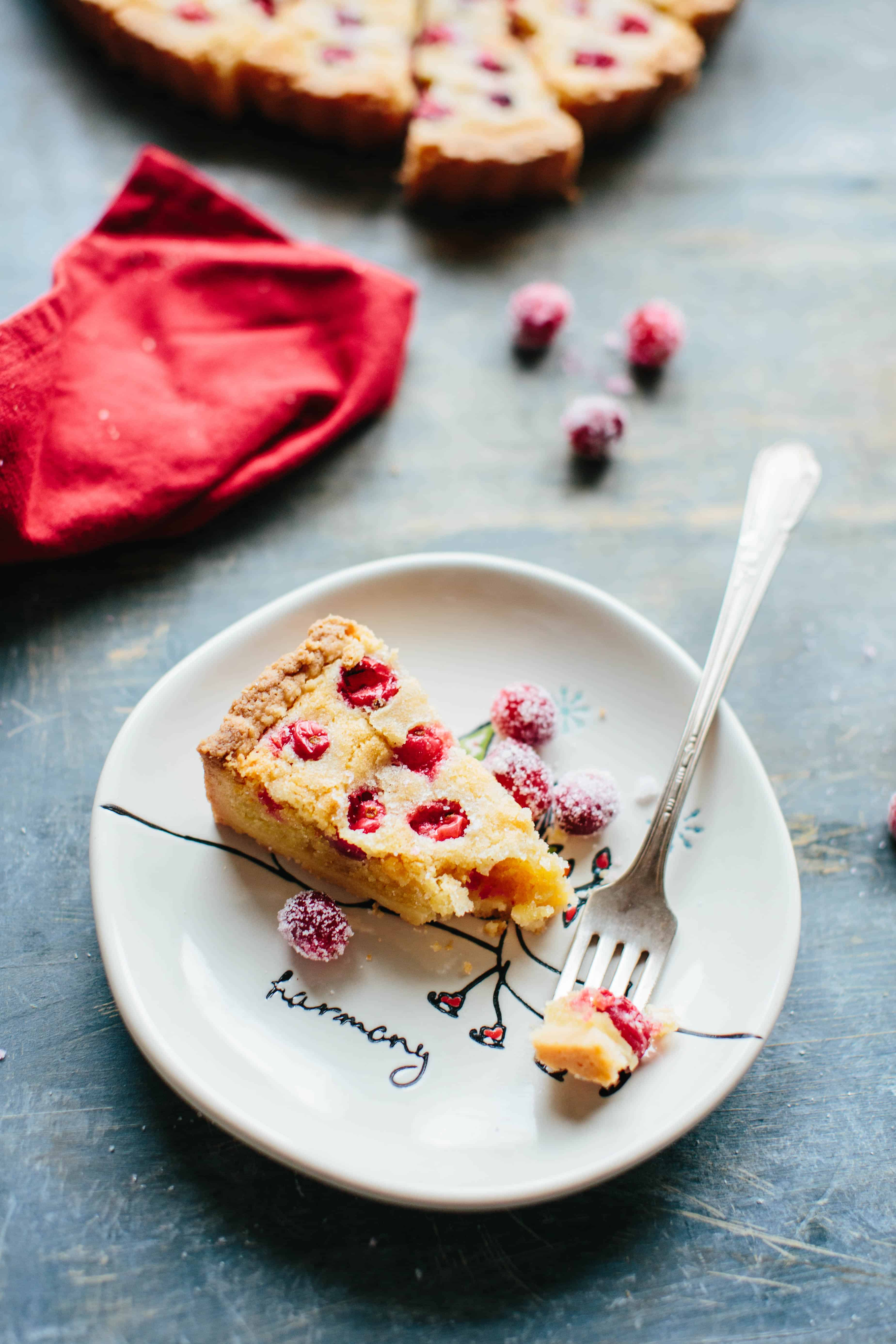 A piece of tart on a plate, with a fork taking a piece