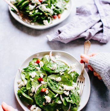 A plate of spinach salad with a fork and a hand