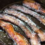 Close up of bacon slices frying in a cast iron skillet.