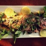 Top view of a whole grilled snapper on a white serving platter.