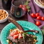 Grilled lamb chops with tomato cucumber salad on a green dinner plate.