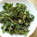 Top view of kale chips in a shallow white bowl.