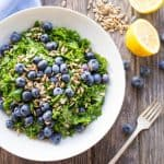 Top view of a white bowl filled with kale and blueberry salad.