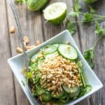 Top view of a square bowl of Thai cucumber salad with a spoon.