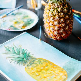 A painting of a pineapple and a real pineapple sitting on a table