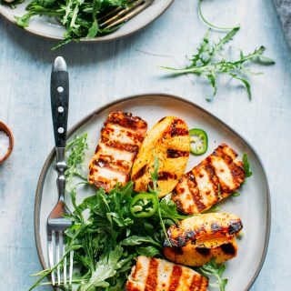 overhead shot of grilled halloumi and peaches with arugula, jalapeños and honey lemon vinaigrette