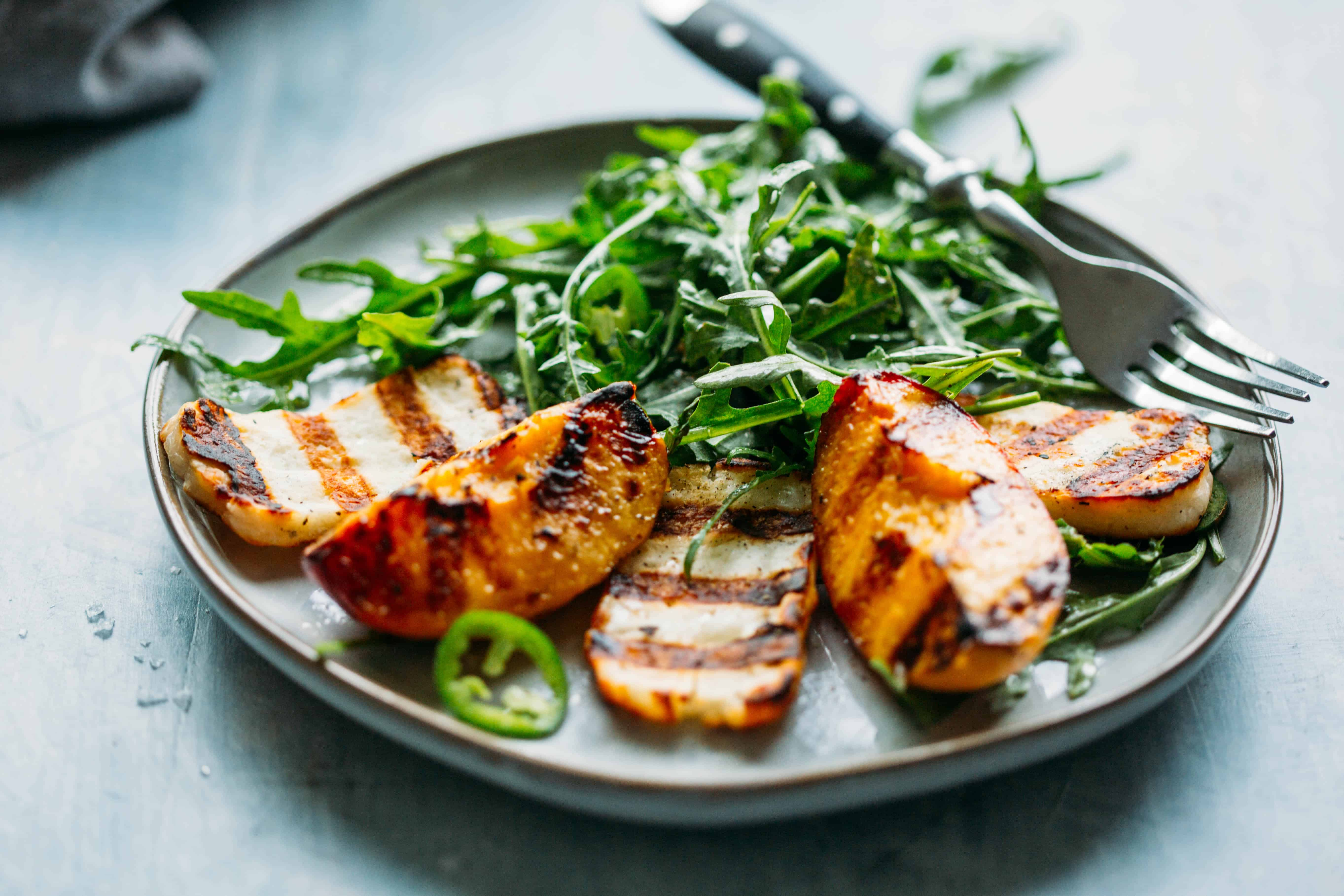 close up of grilled halloumi and peaches with arugula, jalapeños and honey lemon vinaigrette with a fork