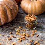 small jar of roasted pumpkin seeds on wood table with seeds scattered around and tan cinderella pumpkins in the background